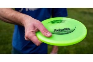 Disc golfer holding Innova AviarX3 disc