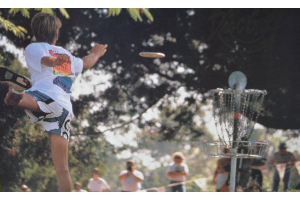 Old photo of a disc golfer putting to basket.