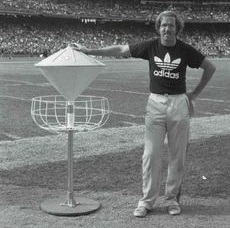 Old disc golfer standing next to historic basket