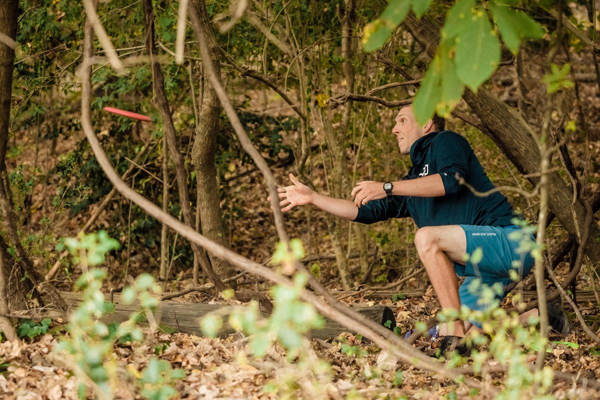 Nate Sexton throwing scramble shot from woods