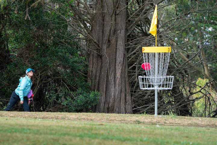 Disc golfer making a long putt