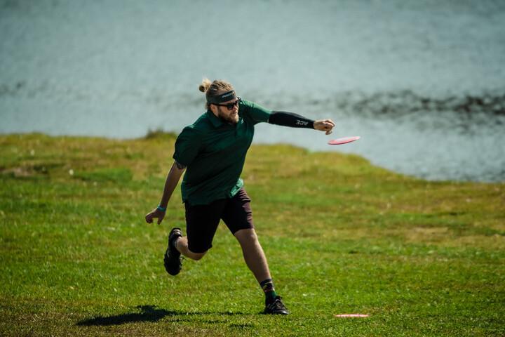 Nathan Queen throwing fairway disc golf shot