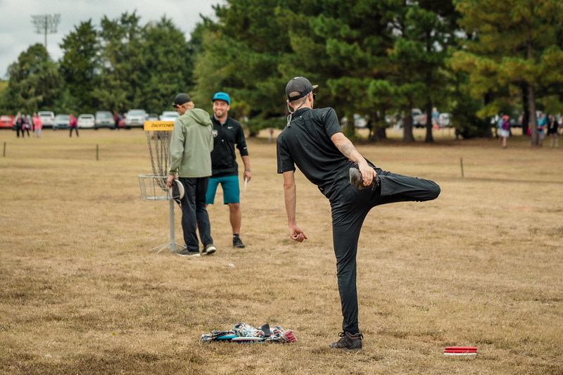 Disc golfer stretching before round
